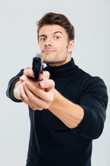 Serious young man standing and aiming gun on you