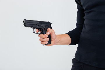 Closeup of man in black clothes holding a gun