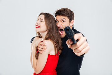 Furious man holding woman and pointing with gun on you