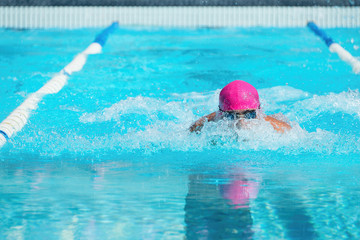 Action shot swimmer swimming breaststroke in the pool