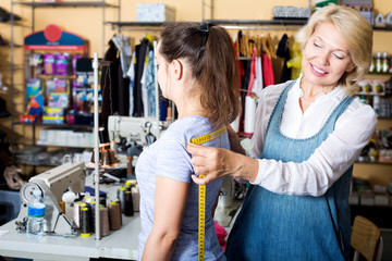 Mature woman customer getting measured by tailor