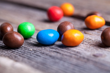 colorful candy in a wooden plate. sweets, icing, nuts