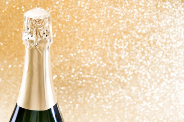 Champagne bottle on brilliant golden background