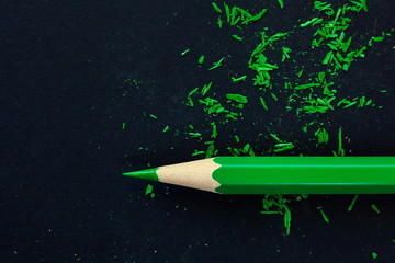 green wooden pencil on black paper background