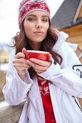 Young woman wearing a sweater and a white hat holding a cup of w