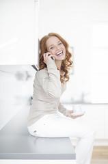rothaarige Frau beim telefonieren in der Küche