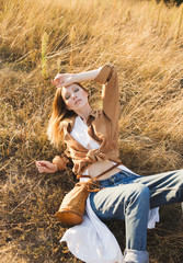 Beautiful blonde in blue jeans, a white shirt and brown jacket is sitting in a field . Boho style