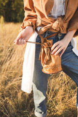 Woman   in blue jeans, a white shirt and brown jacket posing in a field. Boho style. Brown Vintage Bag