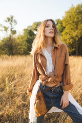 Beautiful blonde in blue jeans, a white shirt and brown jacket posing in a field. Boho style