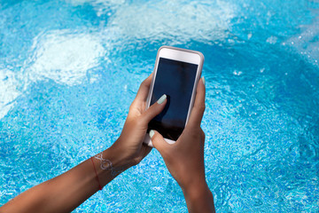 Woman using her phone while sitting at poolside.
