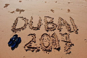 """Dubai 2017"" written in the sand on the beach"
