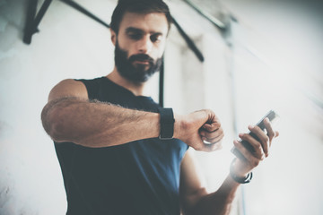 Photo Bearded Sportive Man After Workout Session Checks Fitness Results Smartphone.Adult Guy Wearing Sport Tracker Wristband Arm.Training hard inside gym.Horizontal bar background.Blurred.