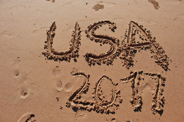 """USA 2017"" written in the sand on the beach"