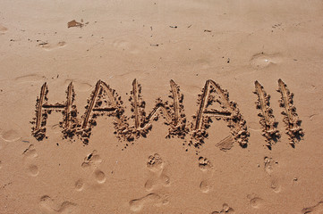 """Hawaii"" written in the sand on the beach"