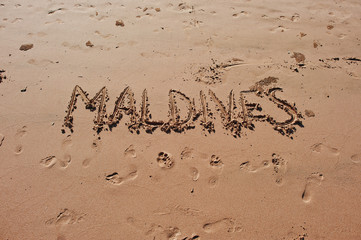 """Maldives"" written in the sand on the beach"