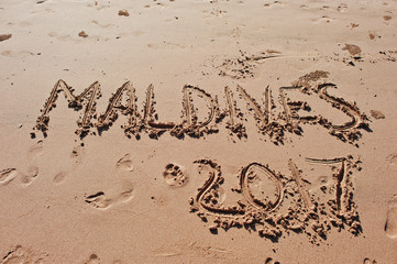 """Maldives 2017"" written in the sand on the beach"