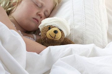 Girl in bed cuddling teddy with bandage
