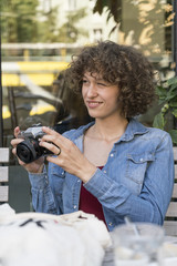 Smiling young woman with old camera sitting in a sidewalk cafe