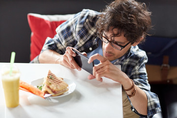 man with smartphone photographing food at cafe