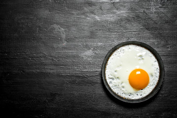 Fried egg in a frying pan. On black wooden background.