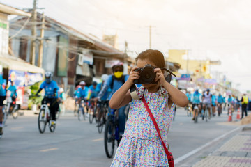 Adorable little girl taking a photo by camera with cyclists ride on road background.