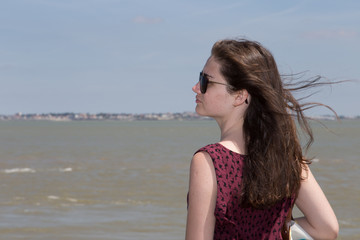 Young girl near the sea. hair in the wind