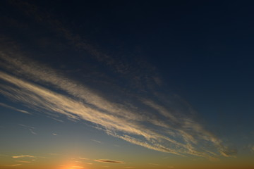 Blue sky white cirrus clouds float to the top at sunset