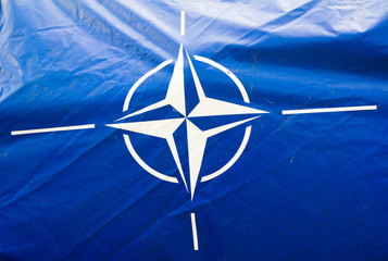 Dirty and wrinkled blue canvas with flag of NATO ( North Atlantic Treaty Organization ). Alliance of defence against enemies