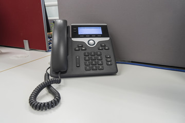 IP phone on white desk and gray partition at office