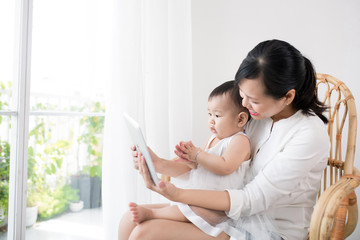 Mother and baby are looking to play and read tablet computer at