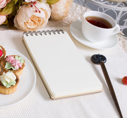 Mockup photography with flowers, notebook, pen and tea