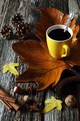Cup of coffee on wooden maple leaf, nuts and autumn leaves