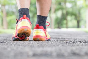 Leg of man walking on road at public park and closeup shoe. Spor