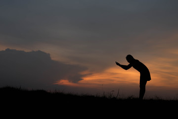 silhouette of woman Standing blessings of god at sunset