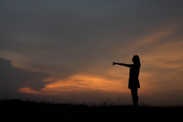silhouette young woman pointing forward to Dream ahead in sunset