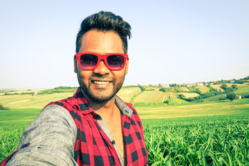 Young indian man taking selfie at green corn field with country hills background - Handsome african guy having fun using modern technology outdoors in a farmland