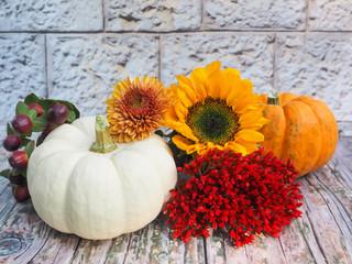 Herbstliches Arrangement mit Kürbissen und Blüten auf hölzernem Untergrund vor steinerner Mauer