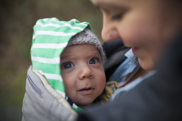 Portrait of a young baby in a child carrier.