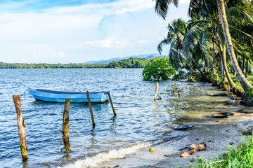 Boat anchored off tropical beach in late afternoon light, Livingston, Guatemala