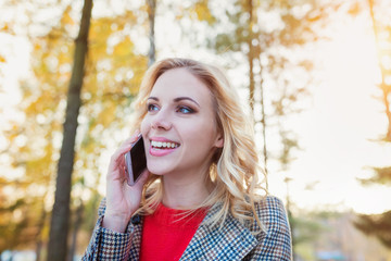 Beautiful woman with smart phone in colorful autumn park
