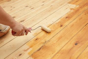 homme mettant huile de protection sur plancher au rouleau