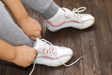Tying Shoe laces girl sitting on the wooden floor. White sneakers on a dark wooden background.Side view.Fitness , sports.