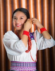 Beautiful hispanic model wearing andean traditional clothing smiling and adjusting decorative hair extension, posing for camera, beige studio curtain background