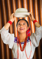 Bautifully dressed hispanic model wearing andean traditional clothing, holding up matching white hat, facing camera smiling, beige studio curtain background