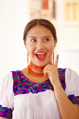 Beautiful young brunette woman wearing traditional andean white blouse with blue decorative edges, facing camera interacting positive, bright household background