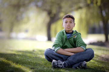 Portrait of a boy sitting with his arms and legs crossed in a park.
