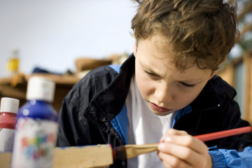 Young boy frowning while painting with a paint brush.