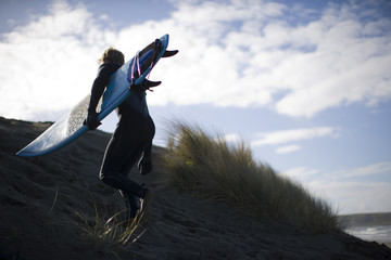 Young man carrying surfboard up sand dune