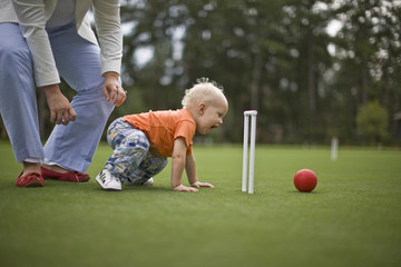 Baby boy pushing croquet ball with his mother crouching above him