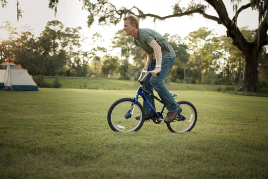 Mid-adult man riding his son's bicycle while camping outdoors.